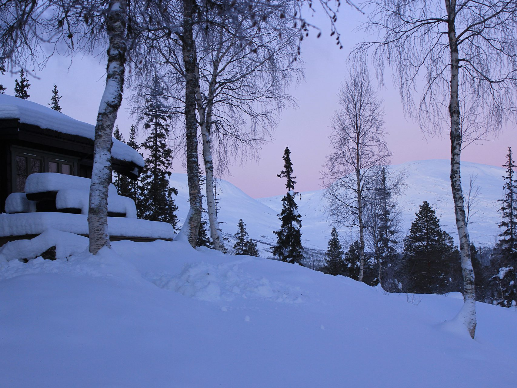 Picture of the outside of a cabin and lots of snow